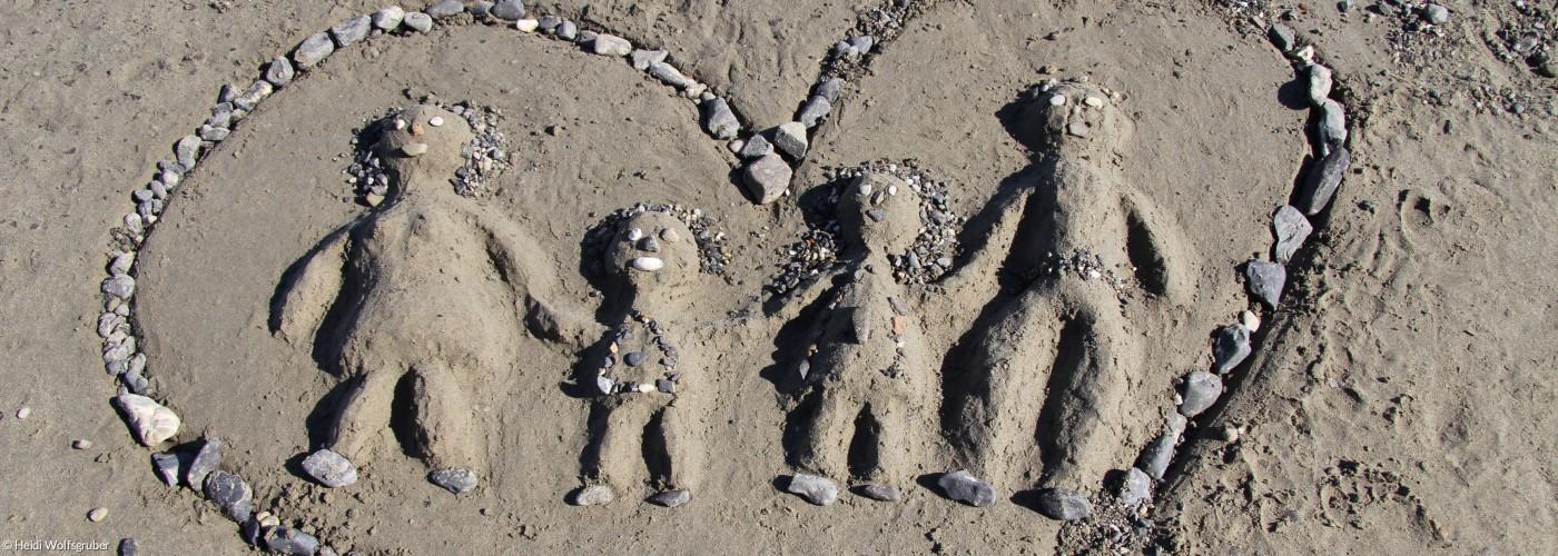 Herz in Sand gemalt mit Vater Mutter Kindern in der Mitte