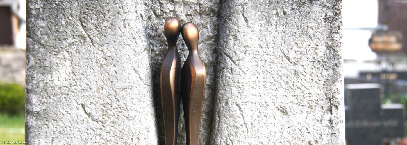 Zwei Bronzefiguren auf einem Grabstein, die sich trostvoll begegnen